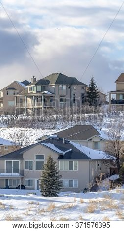 Vertical Frame Homes On Sunlit Wasatch Mountain Slope Blanketed With Pristine Snow In Winter