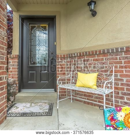 Square Front Door With Decorative Glass Pane At The Facade Of Home With Red Brick Wall