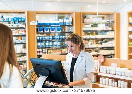 Blonde Female Pharmacist Checks Information On The Computer For A Customer In A Pharmacy
