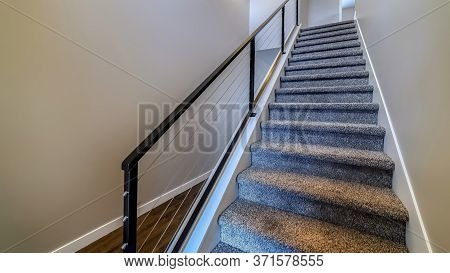 Panorama Indoor Stairs Of Home With Metal Handrail And Gray Carpet On The Treads