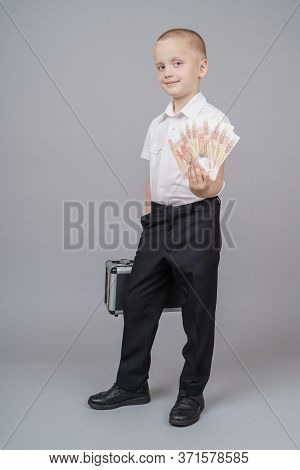 Cute Short-haired Boy Boy 7 Years Old With Black Suitcase, Holds A Pack Of Russian 5000 Rubles In Hi