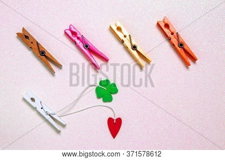 Colorful Set Of Five Wooden And Plastic Clothespins On A Light Pink Glitter Sparkle Background With