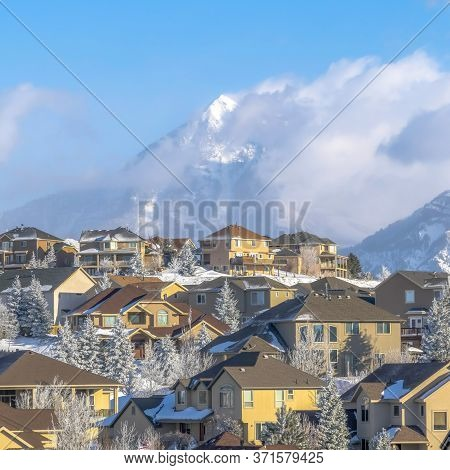 Square Crop Houses With Magnificent View Of Wasatch Mountain Peak Against Cloudy Blue Sky