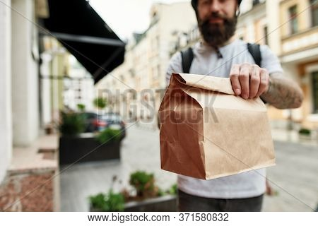 Cropped Shot Of Delivery Man Holding Paper Bag While Giving Away Order To A Customer. Courier, Deliv