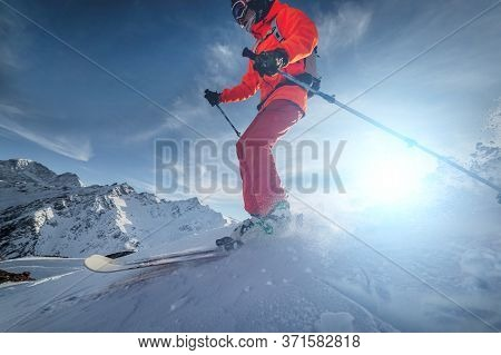 Close Up Skier Rides On A Snowy Slope On A Sunny Day At Sunset Against The Backdrop Of The Mountains