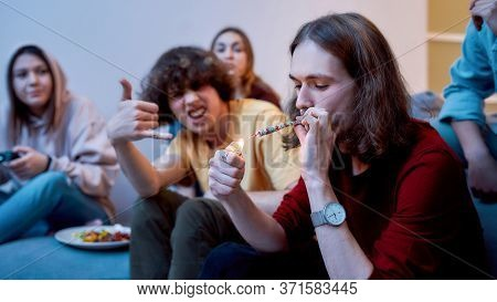 Great Time. Young Teenager, Man Lighting Cannabis Cigarette While Sitting With Excited Friends On Th