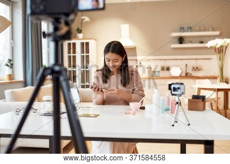 Young Female Blogger Recording A Tutorial Video For Her Beauty Blog About Skincare Routine. Focus On