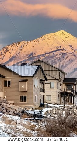 Vertical Crop Houses On Hill With Scenic View Of Wasatch Mountains And Cloudy Sky At Sunset