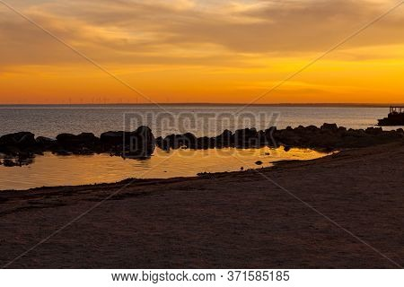 Amazing Golden Sunset On An Empty Beach. Orange And Red Sky Shades. Deserted Seaport On The Shore Po