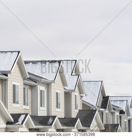 Square Townhouses With Snowy Gable Roofs In South Jordan Utah On A Cloudy Winter Day
