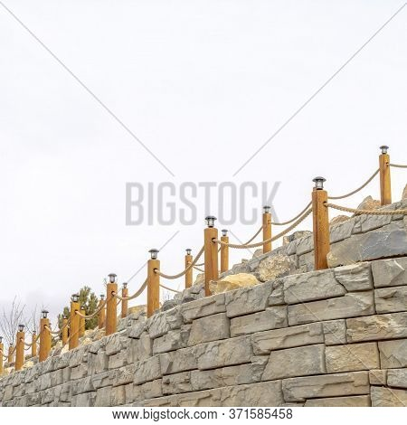 Square Rope Fence With Lamps On Posts Lining A Retaining Wall Made Of Stone Blocks