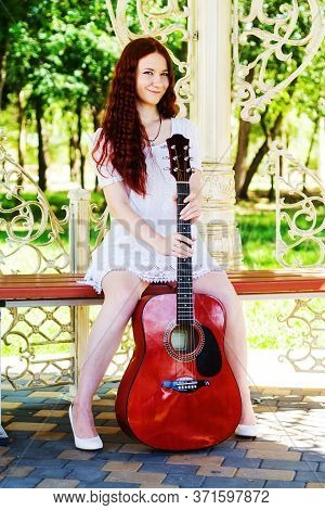 Red-haired Beautiful, Romantic Girl With A Guitar Sitting On A Bench In The Summer With A Beautiful