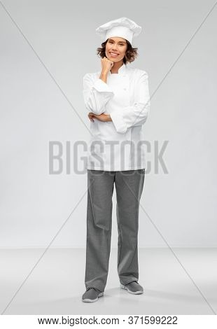 cooking, culinary and people concept - happy smiling female chef in toque over grey background