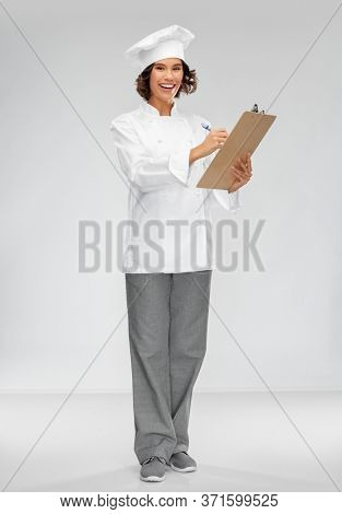 cooking, culinary and people concept - happy smiling female chef in toque with clipboard and pen over grey background