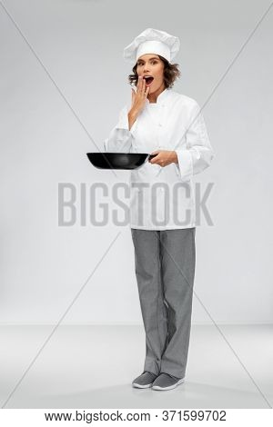 cooking, culinary and people concept - surprised female chef in toque with frying pan over grey background