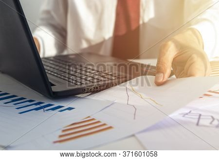Businessman Analyzing Investment Charts With Laptop And Papers On A Sunny Day. Red And Blue Colors.