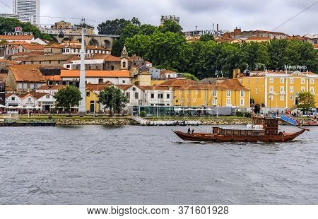 Porto, Portugal - May 30, 2018: View Across The Douro Onto Famous Portuguese Wine Cellars And Touris