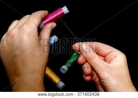 Female Hands Hold Skeins Of Thread. Silk Threads For Embroidery. Skeins Of Yellow, Blue, Green Pink.