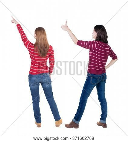 Back view of two pointing girl in sweater. Rear view people collection. backside view of person. beautiful woman showing gesture. Rear view. Isolated over white background.