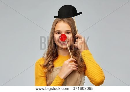 red nose day, party and photo booth concept - smiling teenage girl with red clown nose and bowler hat over grey background