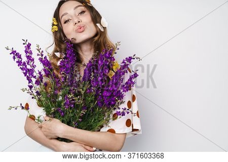 Photo of pleased woman with fake butterflies and flowers making kiss lips aside isolated over white wall