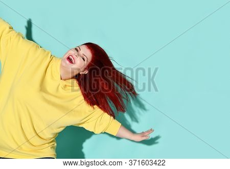 Happy Plump Female With Flowing Red Hair Dancing Or Jumping With Her Arms Outstretched Widely Like W