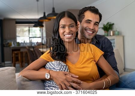 Portrait of happy young indian couple relaxing together on sofa. Middle eastern couple cuddling at home while looking at camera. Portrait of lovely man embracing from behind his beautiful girlfriend.