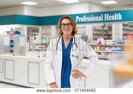 Portrait of woman pharmacist at pharmacy wearing lab coat with stethoscope. Happy mid adult healthcare worker standing in drugstore. Young pharmacist owner standing in store and looking at camera.