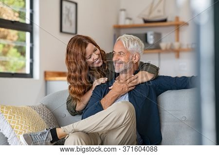 Smiling woman hugging her husband from behind in the living room. Loving mature couple sitting on couch and looking at each other. Mid adult beautiful woman embracing smiling senior at home.