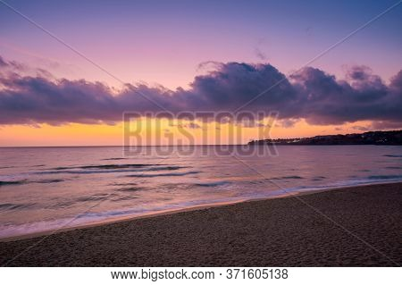 Sea Scenery At Sunset. Beautiful Landscape Of Sandy Beach In Purple Dusk. Wave Running On To The Sho