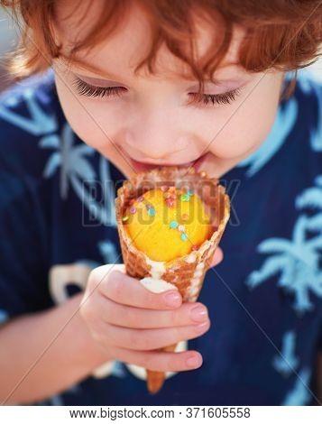 Happy Redhead Boy Eating An Ice Cream In A Cone