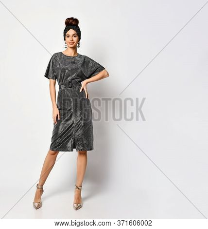 Gorgeous Young Female With Pinned-up Hair Posing In Stylish Headband And Shiny Charcoal Dress With B