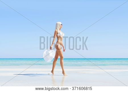 Young And Beautiful Blond Woman Posing In Bikini On The Beach. Fit And Sexy Fashion Model In Swimsui