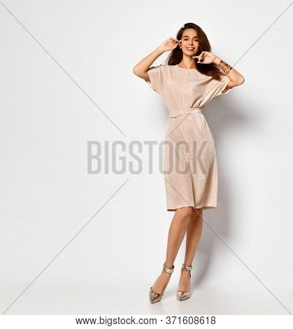 Cute Lady With Flying Long Hair Standing Cross-legged In Delicate Pink Short Dress And Silver Stilet