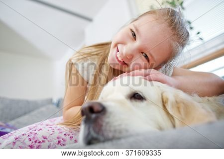 Happy girl cuddles with golden retriever dog on sofa at home
