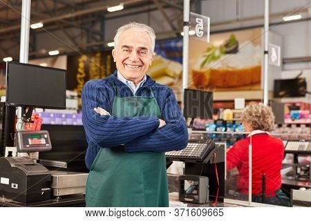 Smiling senior as a market manager with crossed arms in the supermarket