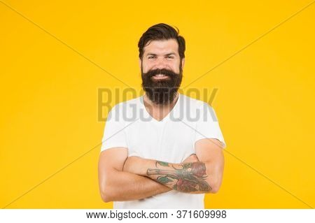 Happy Brutal Bearded Man On Yellow Background. Handsome Confident Man Has Perfect Hairstyle. Male Fa