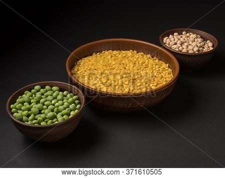 Organic Green Peas, Yellow Lentils And Chickpeas On A Black Background.