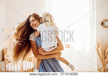 Young Mother Or Babysitter With A Little Girl In Her Arms Spin In The Middle Of The Room