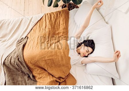 Lifestyle Portrait Of A Happy Young Girl Waking Up And Stretching In Bed Early In The Morning