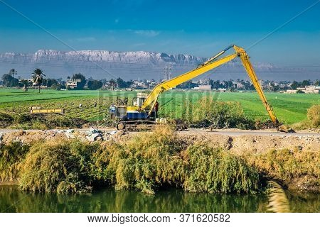 Egyptian countryside near the Nile irrigation canal . Green landscape,  palm trees and earth digging excavator in the Nile Valley. Egypt.