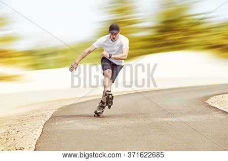 Aggressive Inline Skating. Young Sporty Man Is Rollerblading