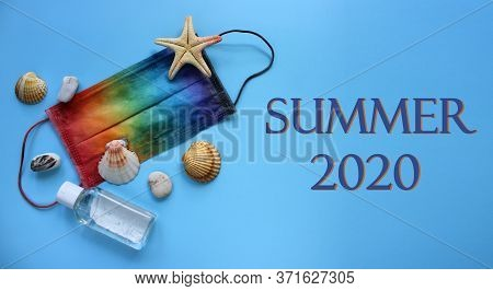 Summer Vacation Flat Lay With Seashells, Pebbles And Starfish On Protective Mask Decorated In Rainbo