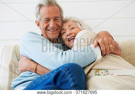 Senior couple embracing sitting on couch half length