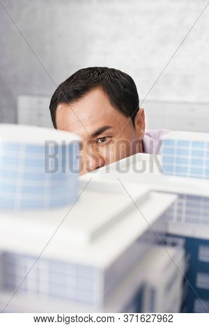 Mid adult man looking at architectural model close-up