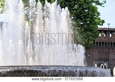 Fountain In Front Of The Entrance To Castle Known As Castello Sforzesco, Milan, Lombardy, Italy. Clo