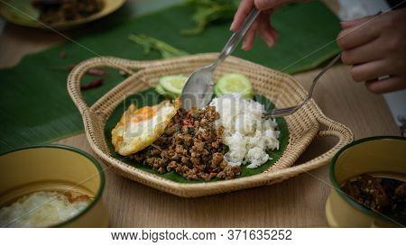 Hands Holding Silverware Eating Thai Traditional Food, Stir Fried Minced Pork With Basil (pad Ka Pra