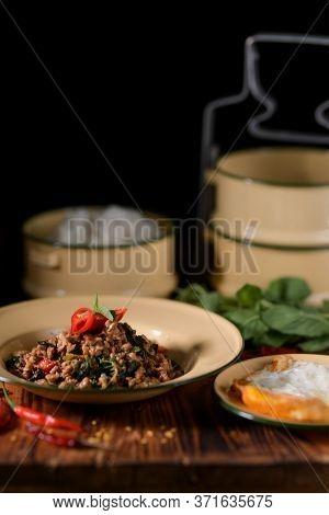 Stir Fried Minced Pork With Basil (pad Ka Prao) And Fried Egg Serving On Vintage Plate On Wooden Kit