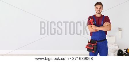 Young Man With Plumber Wrench Near Toilet Bowl Indoors, Space For Text. Banner Design