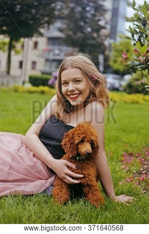A Girl In A Chic Long Pink Dress Is Sitting In The Yard With Her Dog, A Brown Poodle. The Girl Walks